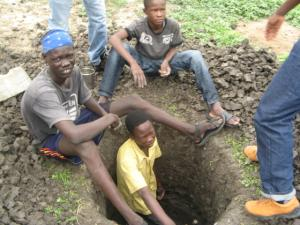 Enthusiastic teenagers digging a pit