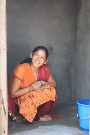 Dahlit woman in Nepal with her latrine