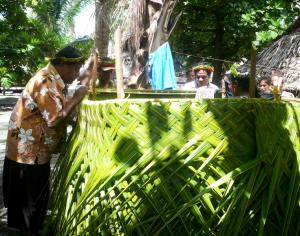 Minister of Public Health inspects a toilet superstrucure made from coconut leaves during Kiribati's ODF celebrations